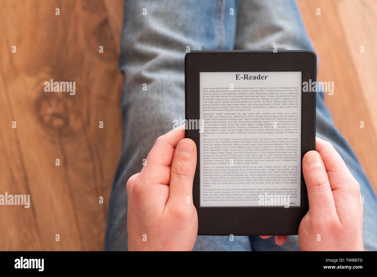 Reading a novel on ebook reader at home - Stock Image