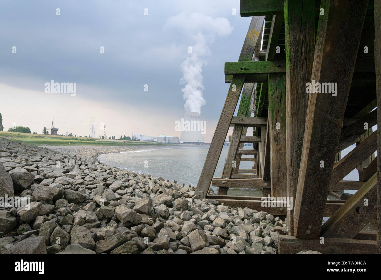 The cooling towers of Doel with left in the picture an old windmill - Stock Image