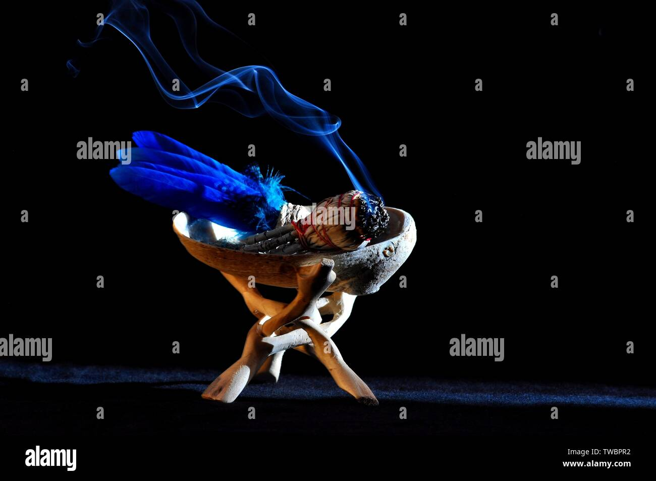 A smudge stick with burning smoke in abalone shell (spiritual concepts) - Stock Image