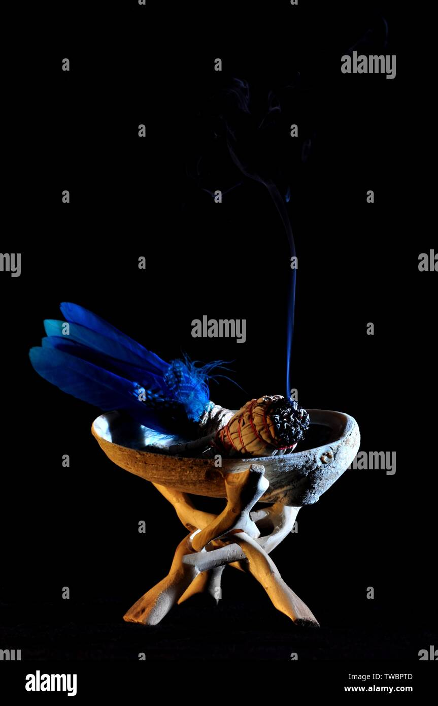 A smudge stick with burning smoke in abalone shell (portrait) - Stock Image