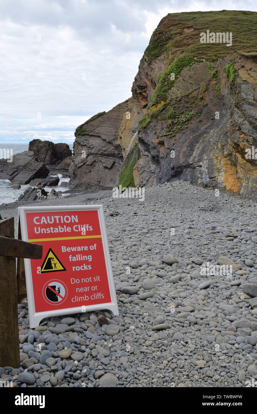 Warning sign under cliff base on beach regarding the danger of unstable cliff and falling rocks - Stock Image