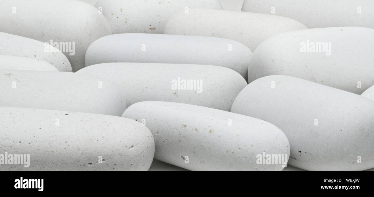 background of white smooth stones of elongated shape - Stock Image