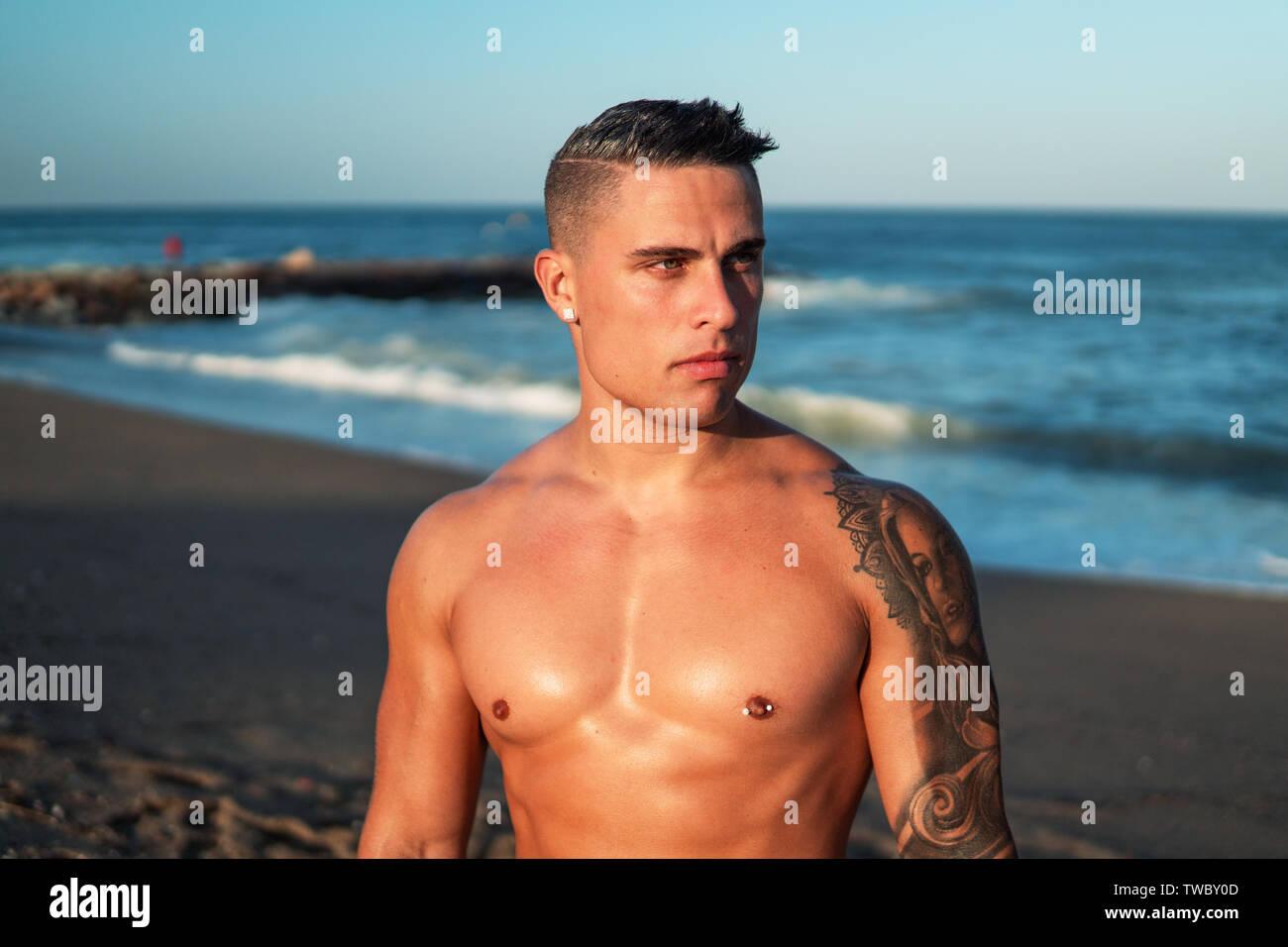 Tattooed bodybuilder sexy male coach at the beach. Stock Photo