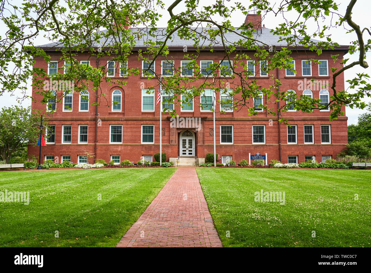 red brick Romanesque Revival building that is the Barnstable Town Hall framed by branches of a beautiful old tree - Stock Image