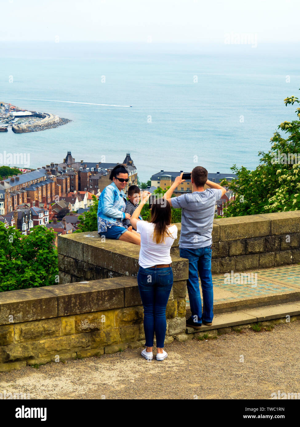 Spanish Tourists on holiday in Scarborough North Yorkshire taking photographs of their children on the look out point at Olivers Mount above the town - Stock Image