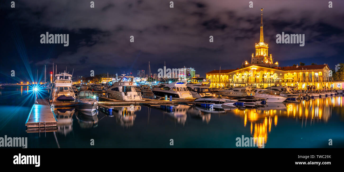 Marine Station of Sochi, illuminated with lights at night with reflection in water. Yachts and boats at the pier - Stock Image