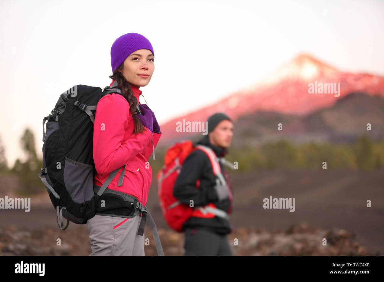 Hiking people on mountain. Hiker couple walking with backpack in high altitude mountains. Young woman hiker in focus trekking at sunset Tenerife, Canary Islands, Spain. - Stock Image