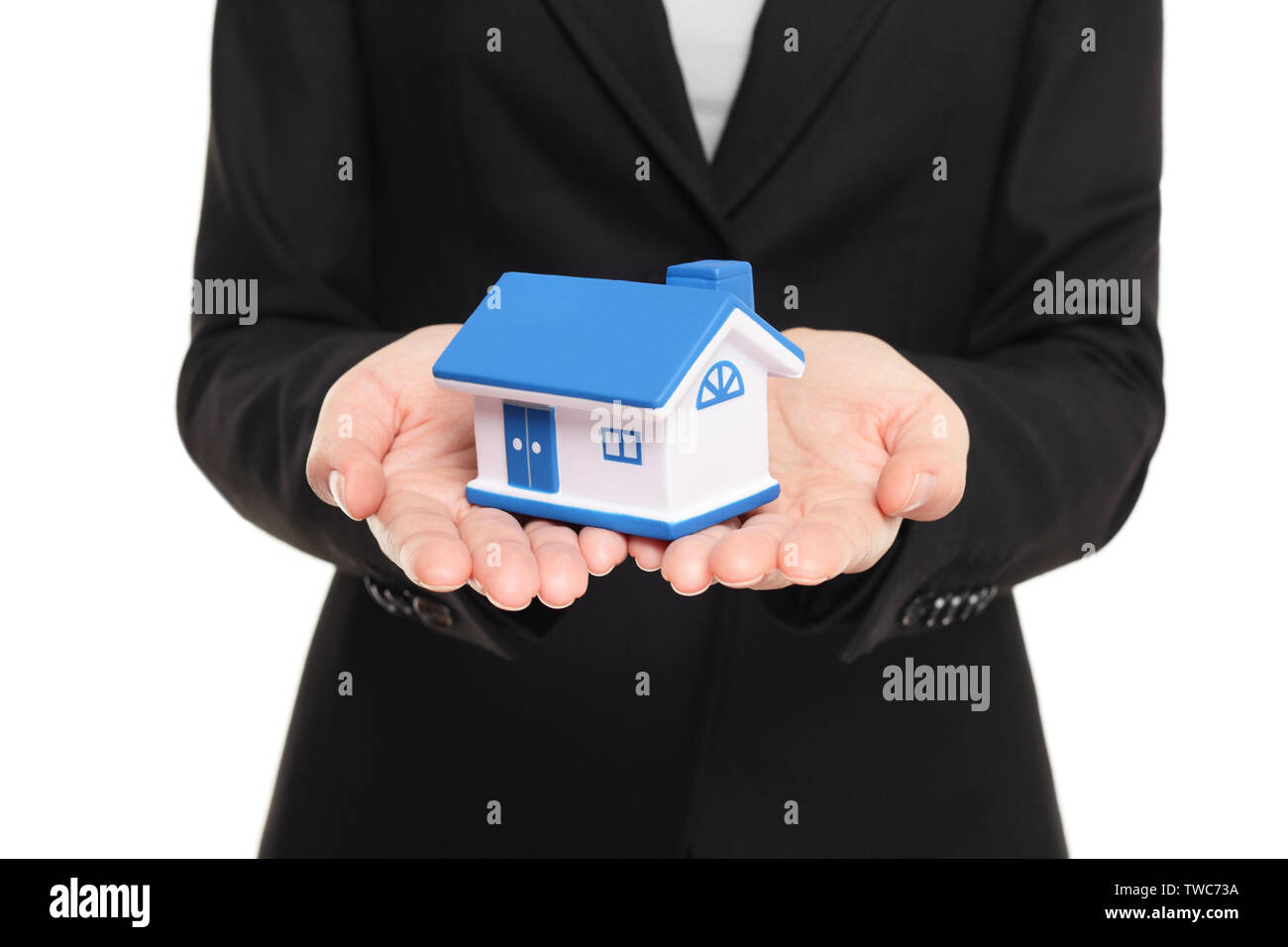 Real estate agent showing new house in mini size. New home owner concept. Realtor showing holding house model. Buying new home conceptual image with business woman in suit isolated on white background Stock Photo