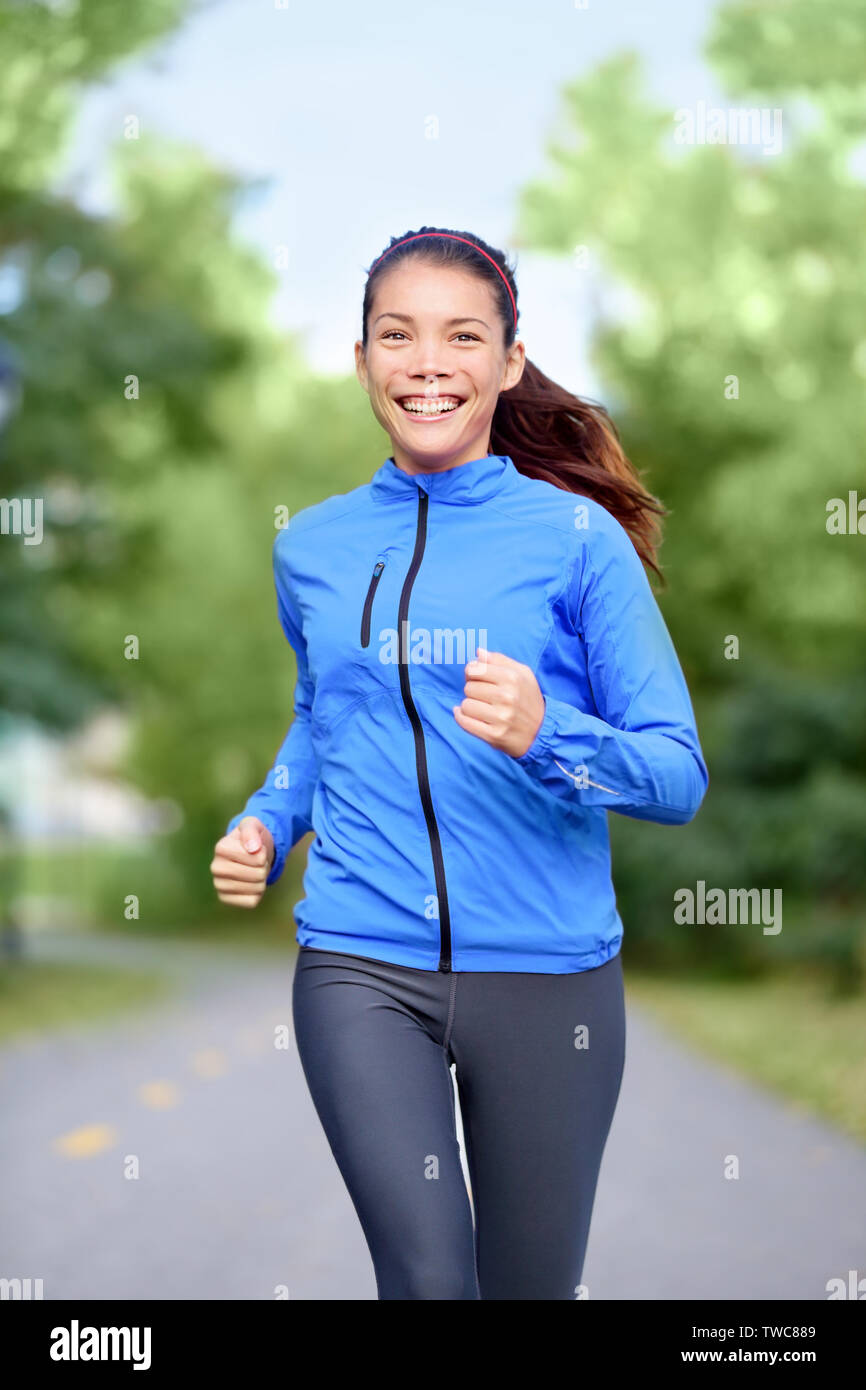 Happy woman runner healthy lifestyle concept with girl jogging smiling training outside in park for marathon. Beautiful mixed race Asian Caucasian female model fresh and vivacious. - Stock Photo