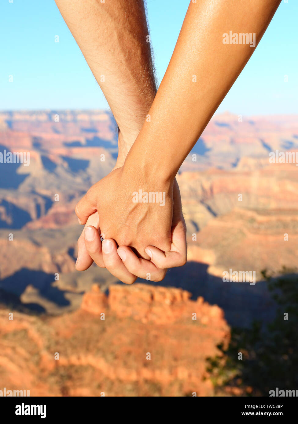 Couple holding hands hiking romantic, Grand Canyon. Close up of young lovers on hike enjoying view and romance. Woman and man hikers. Stock Photo