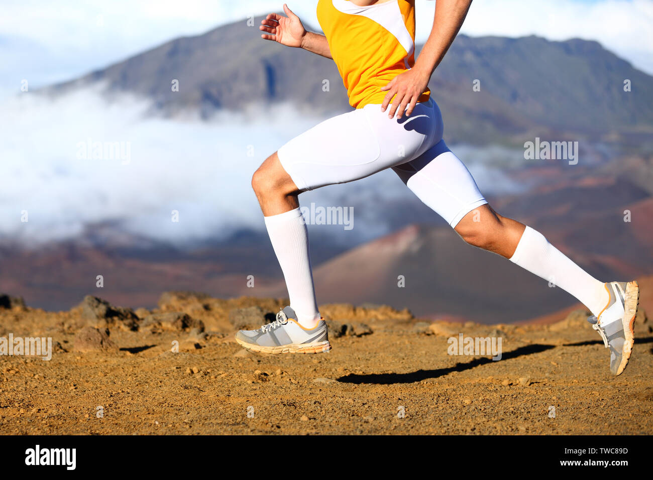 Trail running - male runner in cross country run. Closeup of strong legs and running shoes sprinting at speed. Male athlete fitness runner in compression sports clothing, socks and shorts. - Stock Image