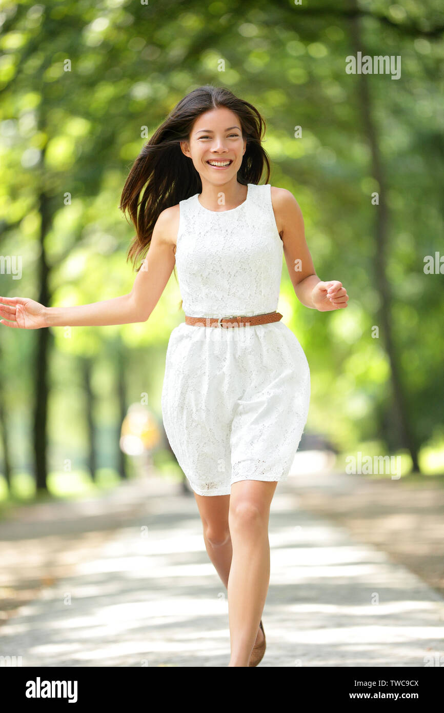 Happy Asian girl running in summer / spring park joyful and smiling in white sundress around trees. Beautiful fresh multiracial Asian Caucasian woman female model in her 20s outside. Stock Photo