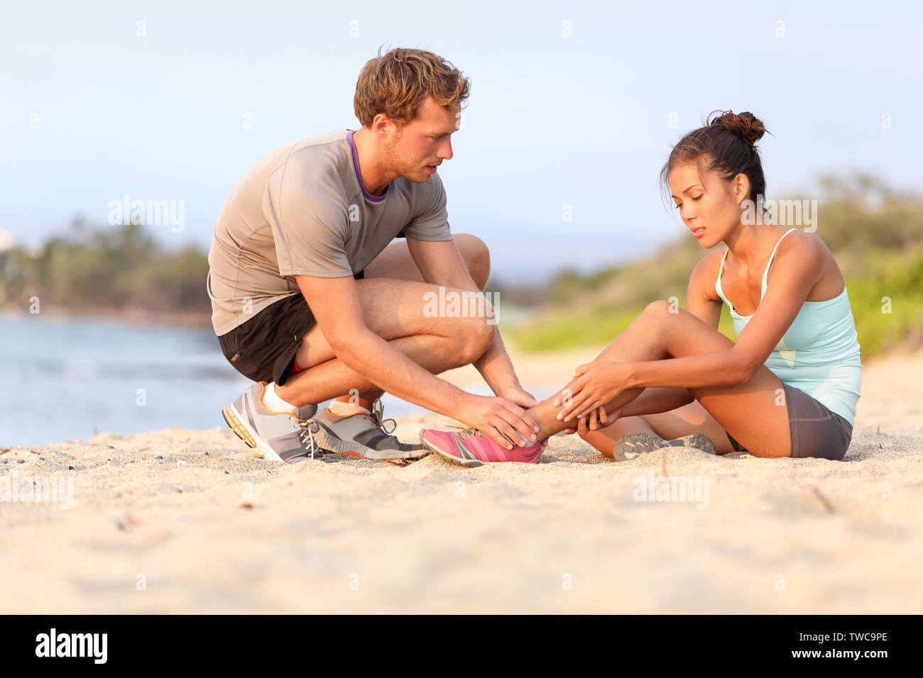 Injury - sports woman with twisted sprained ankle. Asian fitness female model sitting on beach sand getting help from Caucasian male touching her ankle. Stock Photo