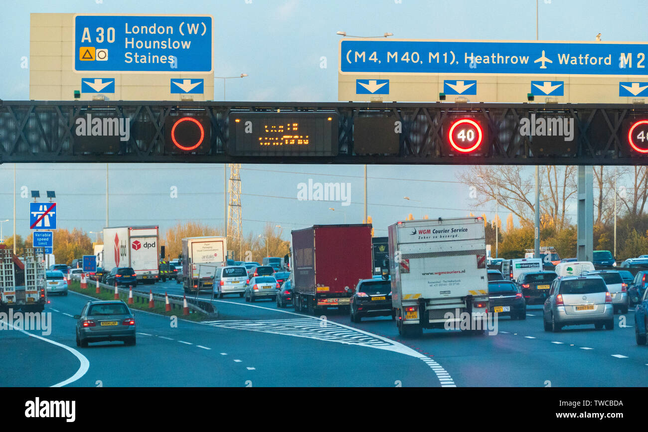 Heavy traffic on M25 London orbital in Middlesex, with A30 slip road and overhead sign showing M4, M40 and M1 motorways in the vicinity. England, UK. - Stock Image