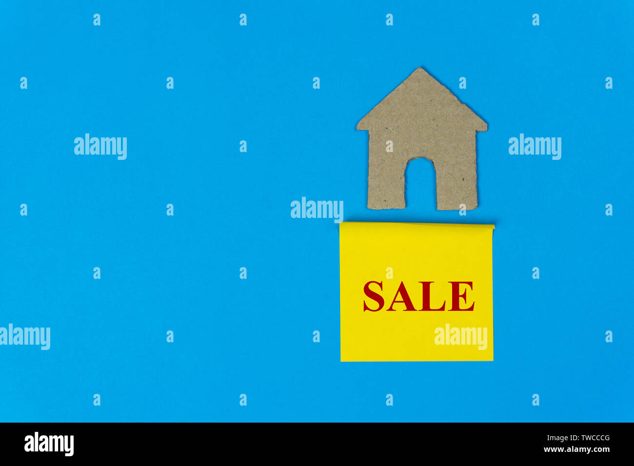 Home for sale. Property sale concept. Real estate sale sign under a small house made by paper cut on blue background. - Stock Image