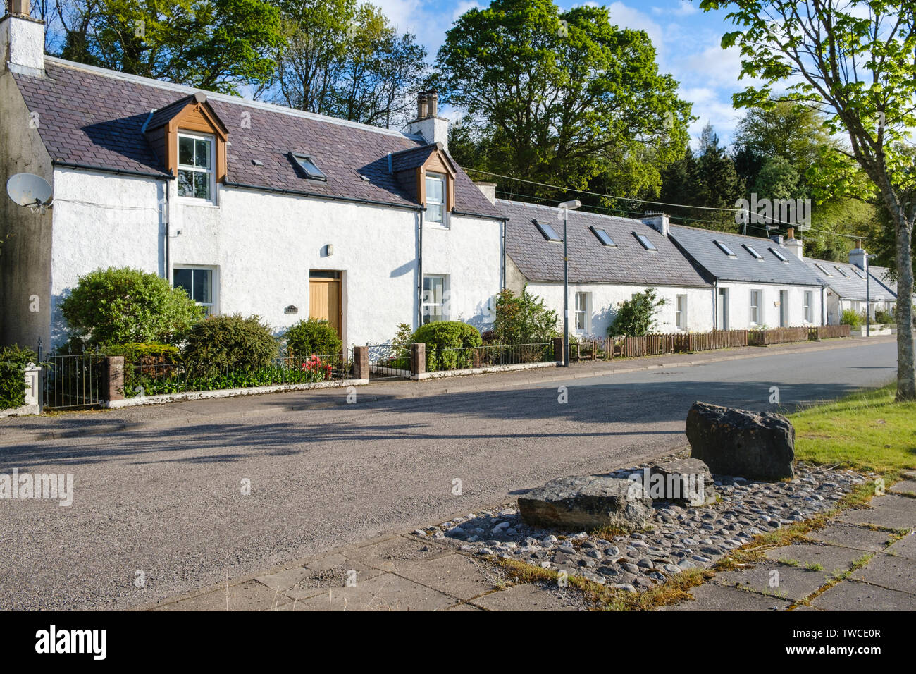 Cottages by the roadside facing Loch Carron in the village of Lochcarron, Wester Ross, Highlands of Scotland. North Coast 500 route. - Stock Image