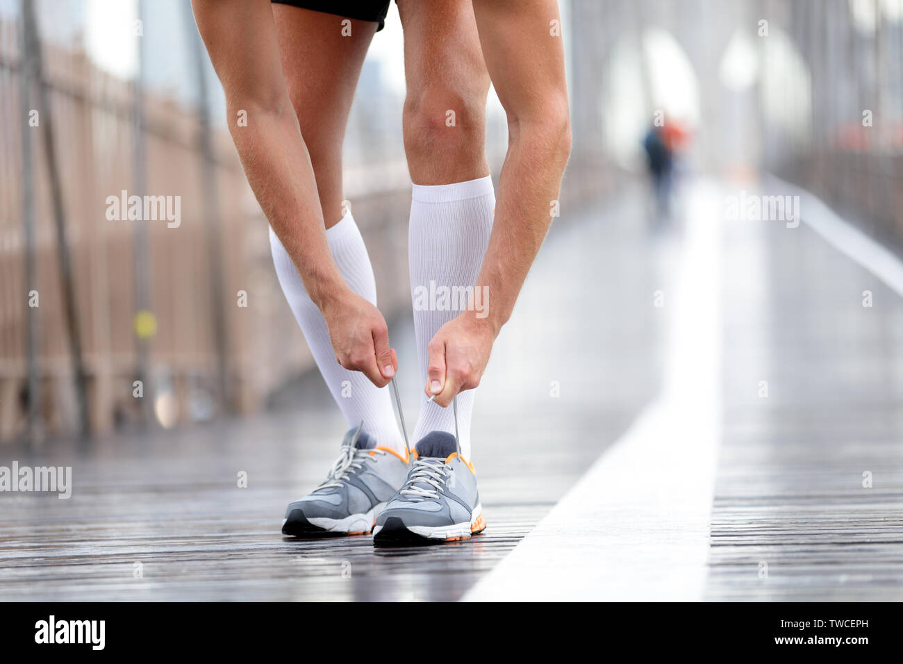 Running shoes - Runner man tying laces, New York City on Brooklyn Bridge. Male athlete runner and feet closeup. Fitness model wearing compression socks. - Stock Image