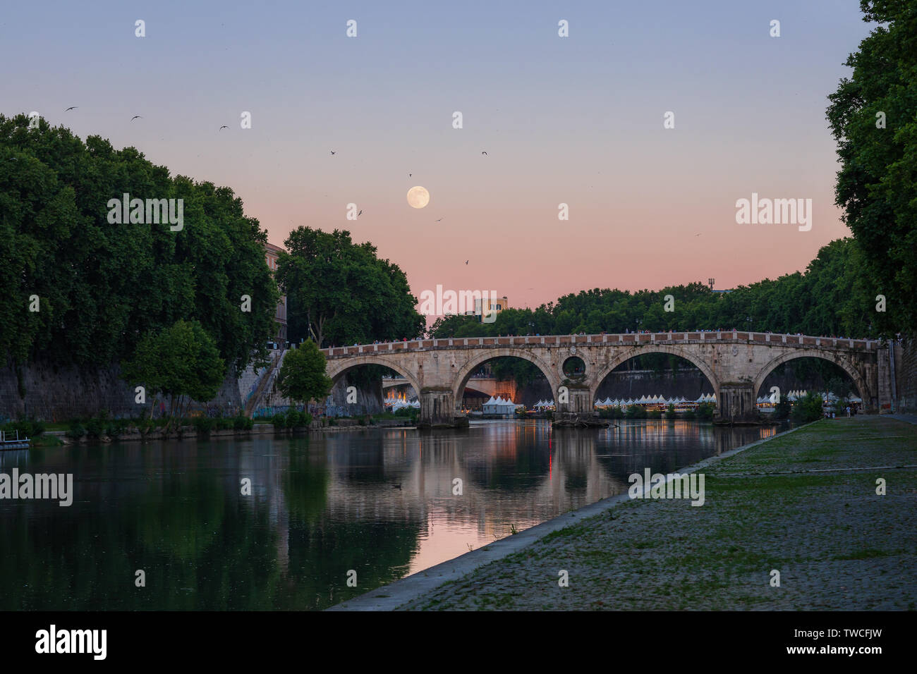 Rome, Italy. Panoramic view of Ponte Sisto at sunset, with the full moon in the background and the Tiber river flowing in the foreground. - Stock Image