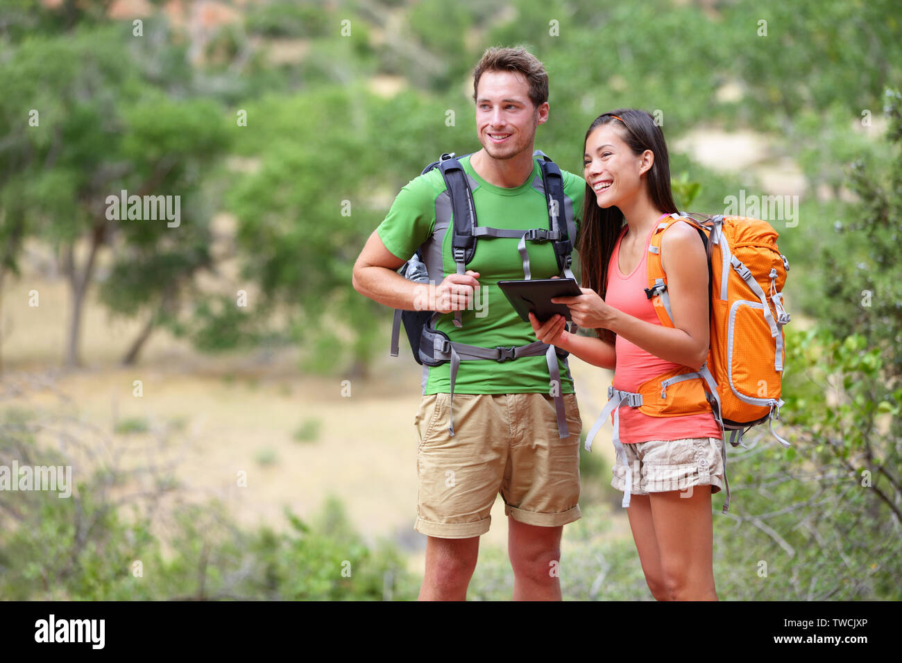 Tablet computer - couple hiking using internet and tablet computer pc guide book app on hike in Zion National Park. Interracial active hiker couple, Asian woman, caucasian man trekking in Utah, USA. - Stock Image