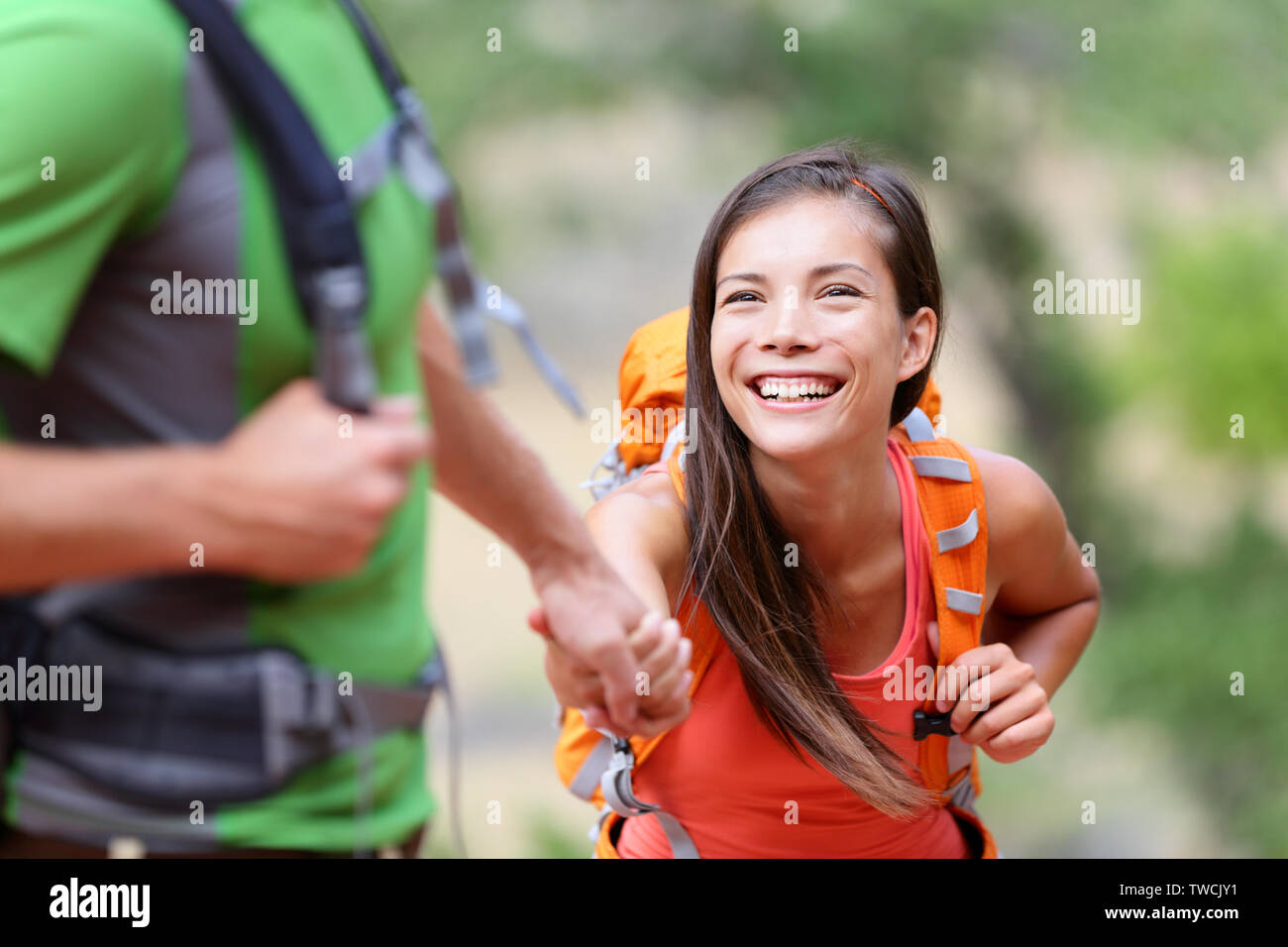 Helping hand - hiking woman getting help on hike smiling happy overcoming obstacle. Active lifestyle hiker couple traveling. Beautiful smiling mixed race Asian Caucasian female model. Stock Photo
