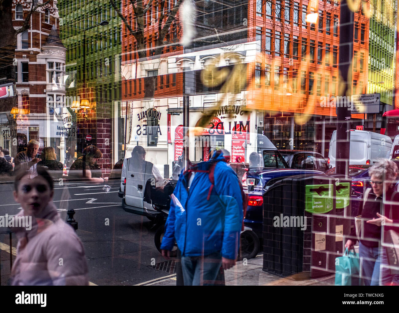 multiple reflections of a busy city in shop window. Stock Photo