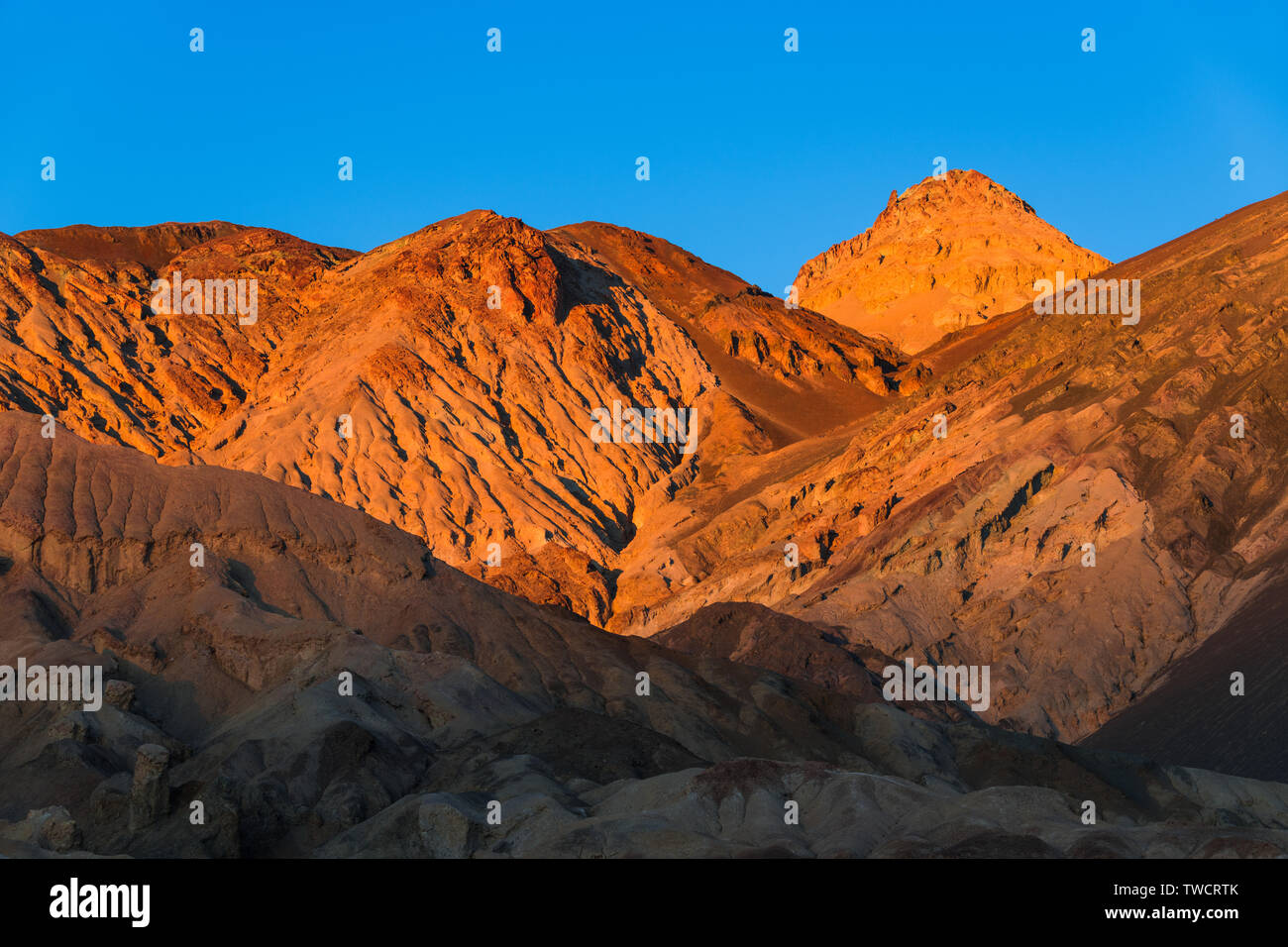 Barren desert mountains and a high peak glow in the golden hour of sunset under a perfect blue sky - Death Valley National Park, California - Stock Image
