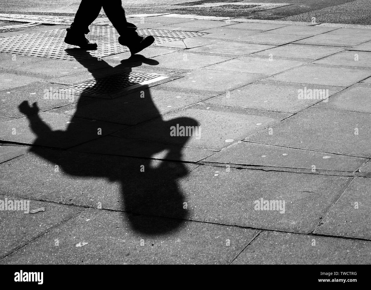 Pavement Shadow of a Person Using a Cell Phone. abstract. Stock Photo