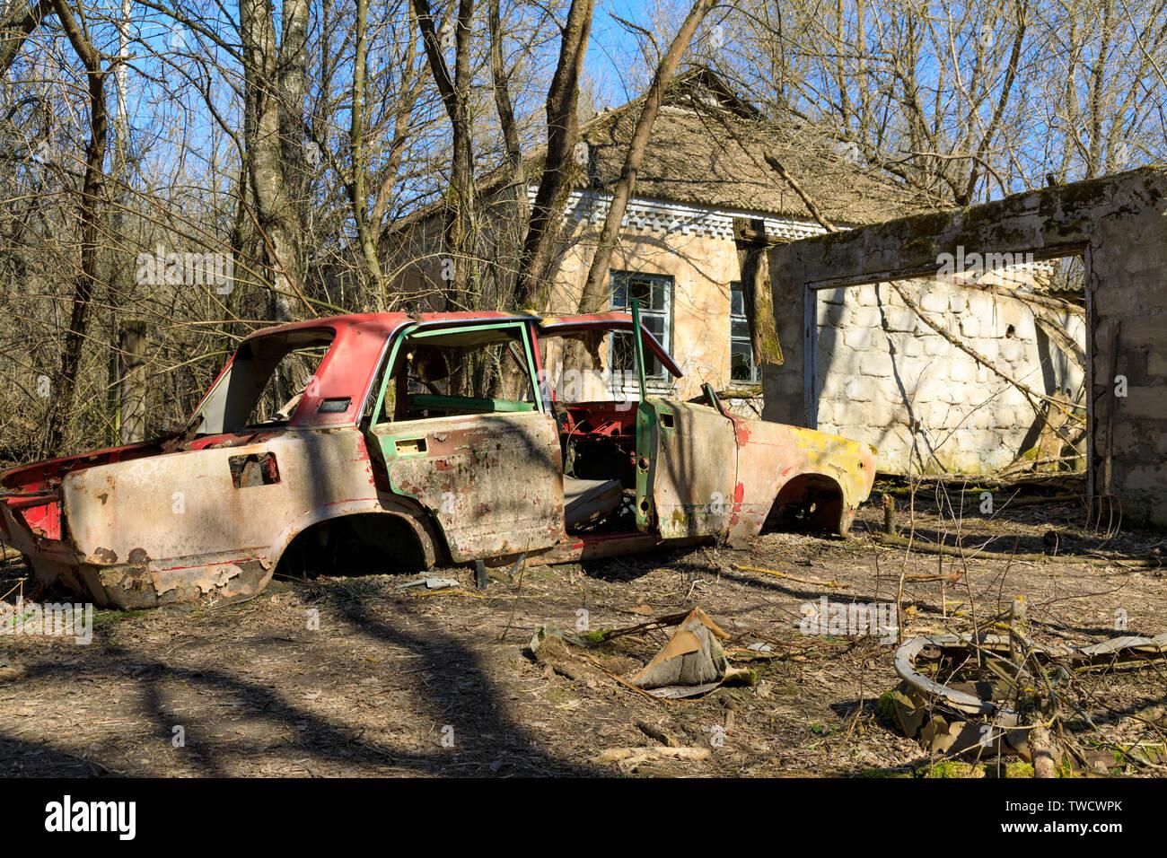 Eastern Europe, Ukraine, Pripyat, Chernobyl. Ruined car. Abandoned house and car. - Stock Image