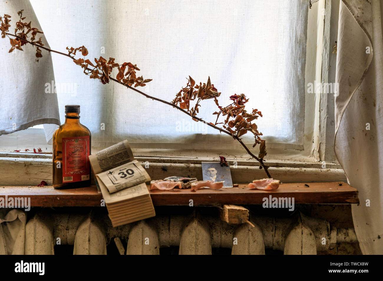 Eastern Europe, Ukraine, Pripyat, Chernobyl. Abandoned house. Window, dead branch,calendar, medicine bottle, dentures on window sill. April 09, 2018. - Stock Image