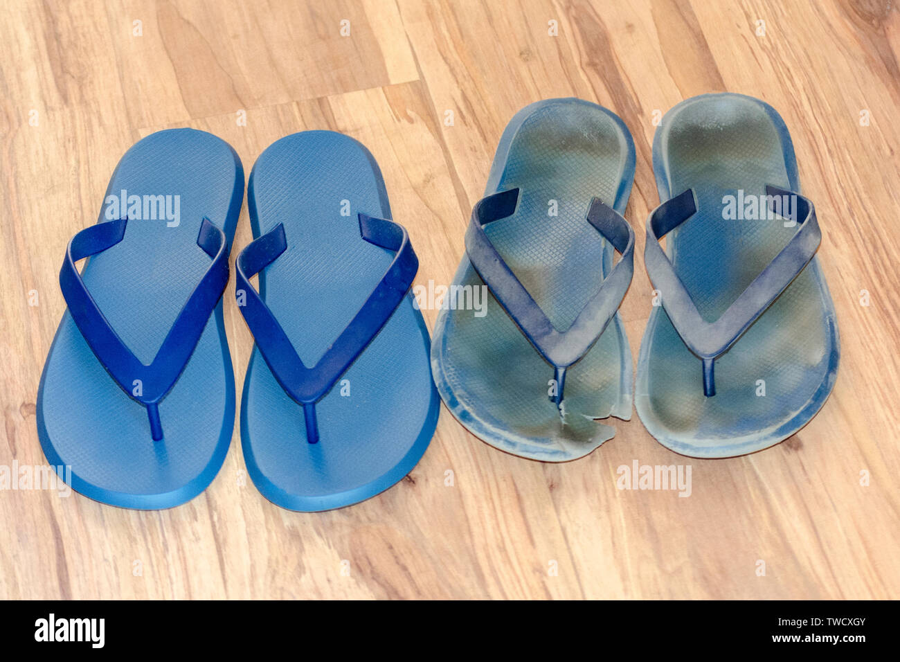 New and old dirty flip flops on light brown floor. Two pairs new and worn out shoes. Blue sandals isolated on wood background. Before and after concep - Stock Image