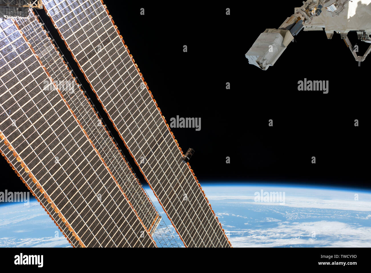 A tiny satellite from Singapore, also known as a CubeSat, is ejected from the Japanese Small Satellite Orbital Deployer past the solar array of the International Space Station June 17, 2019 in Earth Orbit. - Stock Image
