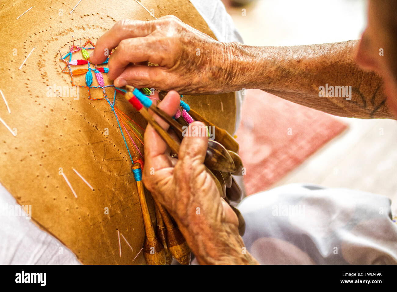Hands of an artisan woman doing bobbin lace work in Sambaqui, at Santo Antonio de Lisboa district. Florianopolis, Santa Catarina, Brazil. - Stock Image
