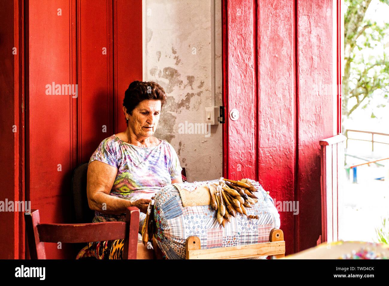 Artisan woman doing bobbin lace work in Sambaqui, at Santo Antonio de Lisboa district. Florianopolis, Santa Catarina, Brazil. - Stock Image