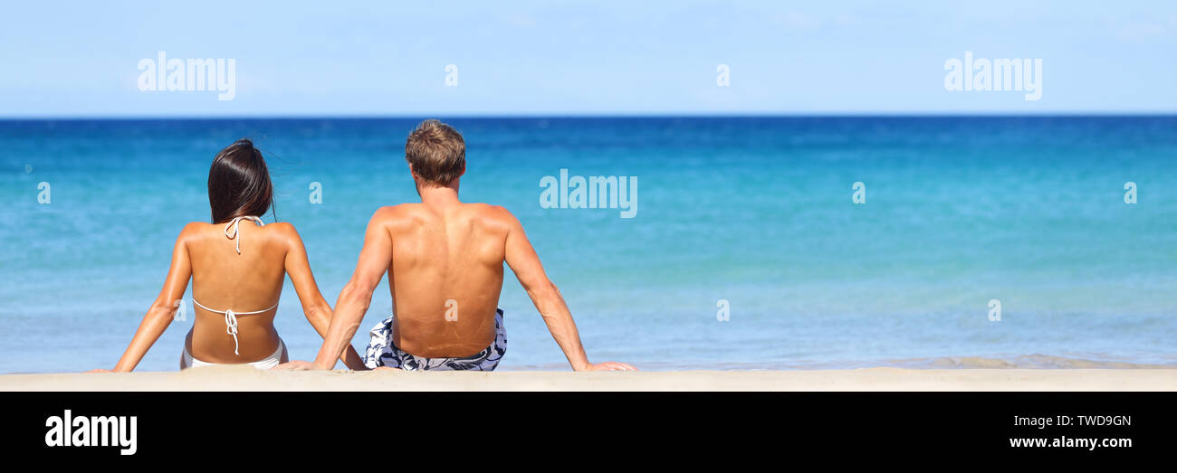 Beach travel banner - romantic couple relaxing on vacation enjoying ocean view together sitting in the sand embracing and hugging. Beautiful young multiracial couple, Asian woman, Caucasian man. - Stock Image