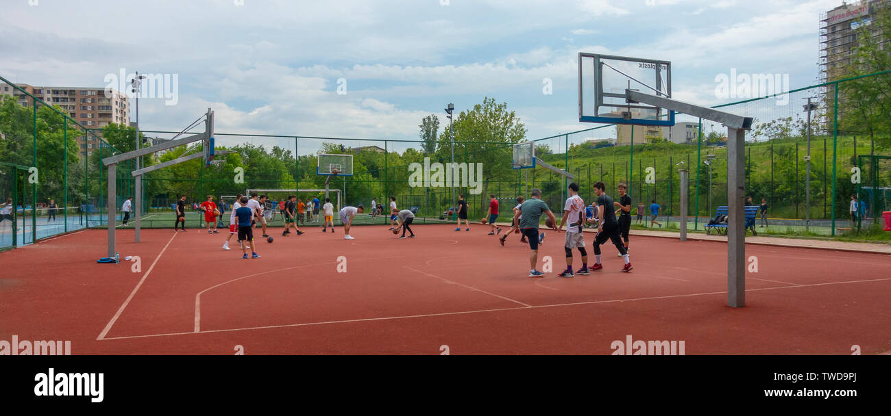 Teen boys practising their basketballs moves with the help of a coach, in the Parcul Lumea Copiilor, Children's World Park, in central Bucharest. - Stock Image