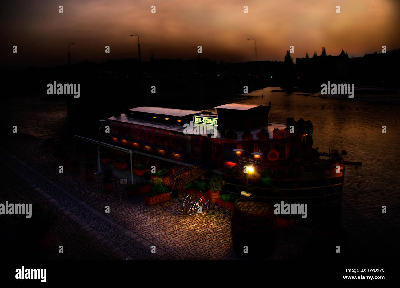 Prague, Czech Republic - October 8, 2008: Barge anchored to the river Moldava converted into a restaurant, night image digitally retouched.... - Stock Image