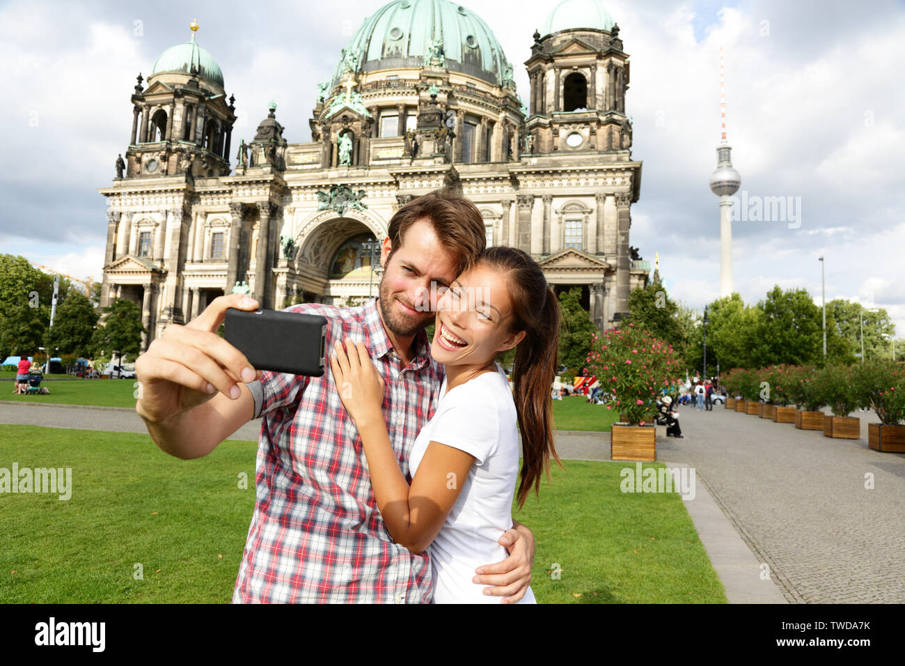 Berlin Germany travel couple selfie self portrait. Happy tourists people in front of Berlin Cathedral / Berliner Dom with Fernsehturm / Berlin TV Tower in the background. Asian woman, Caucasian man. Stock Photo