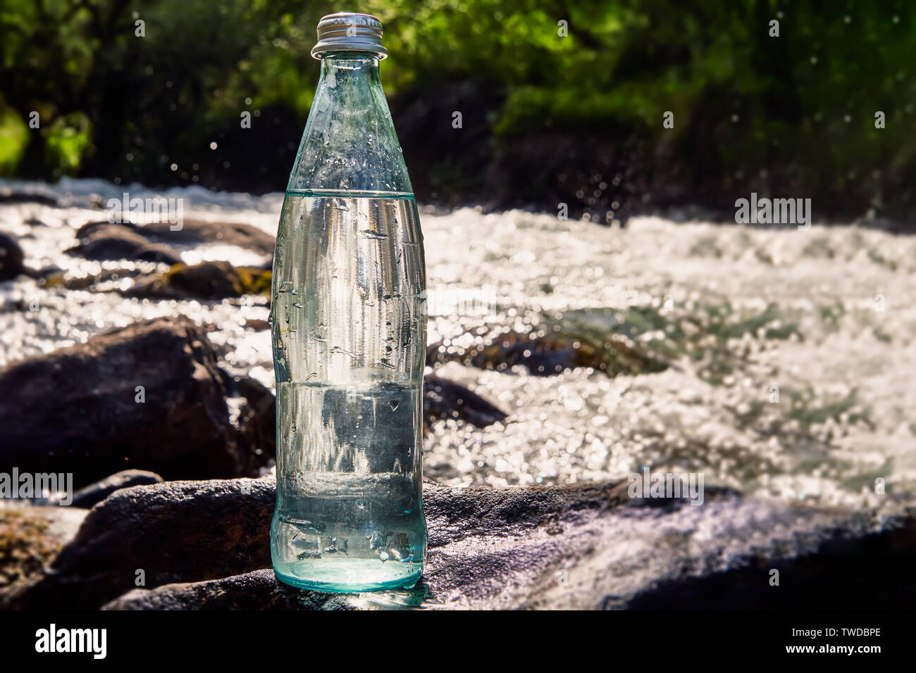A bottle of fresh, cool water against the backdrop of nature, a mountain river with the purest water. Stock Photo