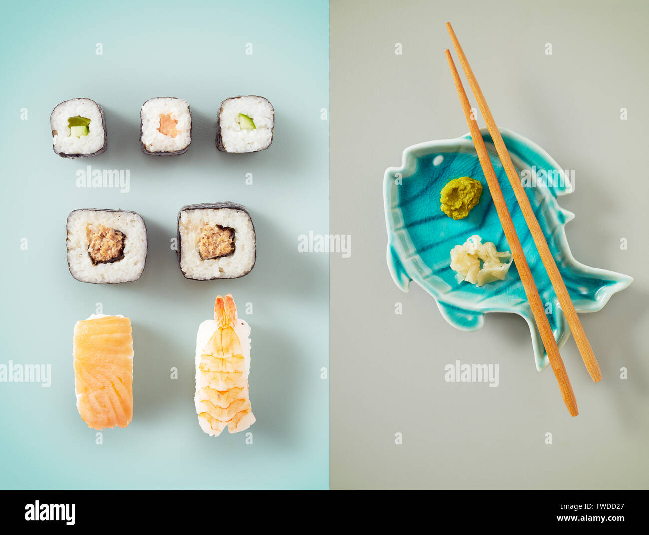 Seaweed wrap filled with avacado next to sushi and blue fish plate holding chopsticks and wasabi sauce - Stock Image