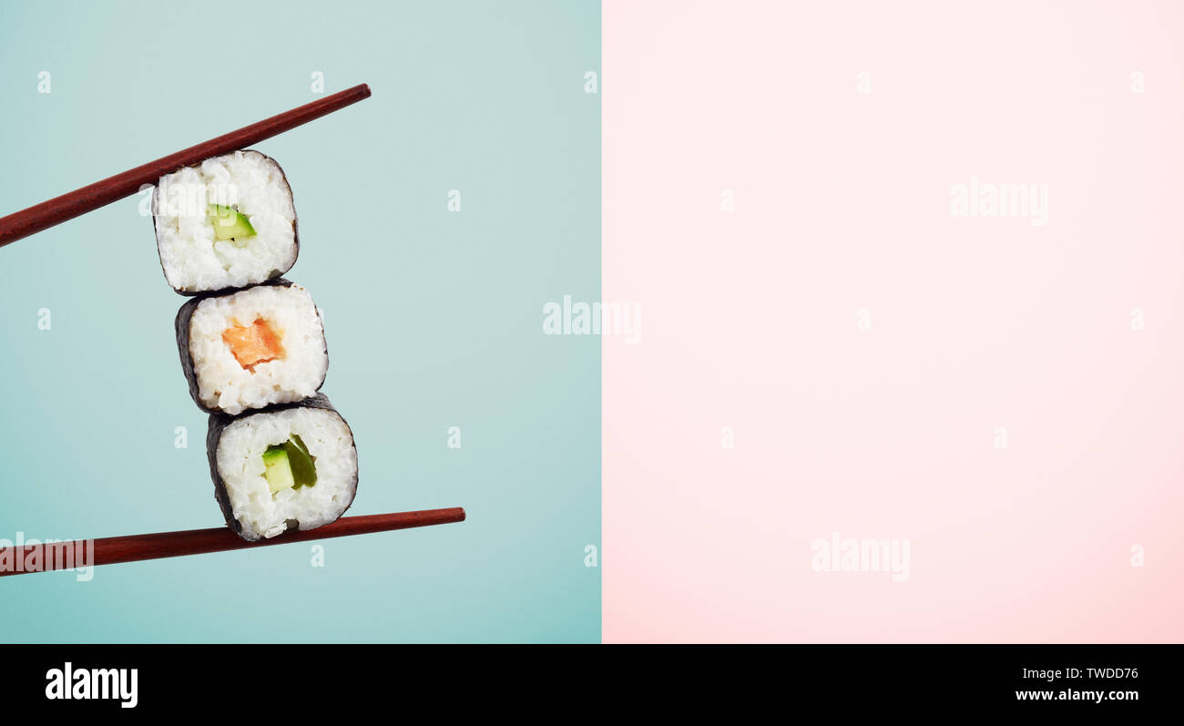 Chopsticks holding three seaweed wraps with rice and avocado over blue half of two tone background. Has copy space. - Stock Image