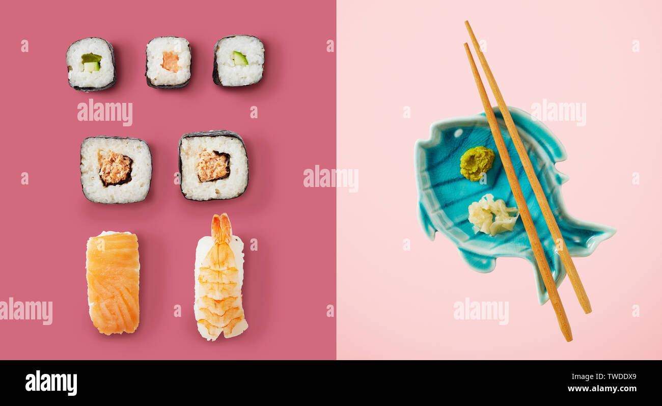 Sushi and avocado rice rolls next to fish plate holding chopsticks and green wasabi sauce over two tone pink background - Stock Image