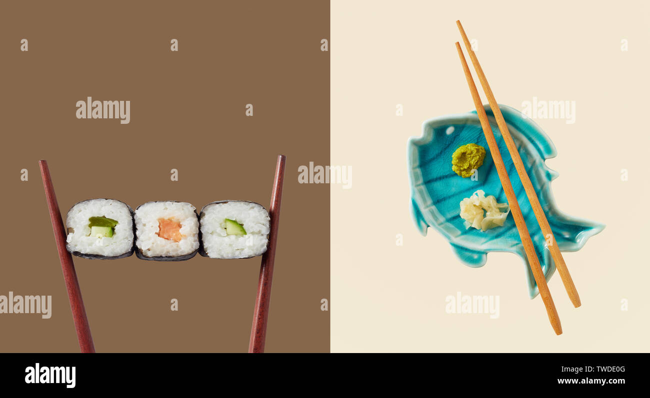 Chopsticks holding three seaweed wraps with rice and avocado next to blue fish shaped plate with sauce - Stock Image