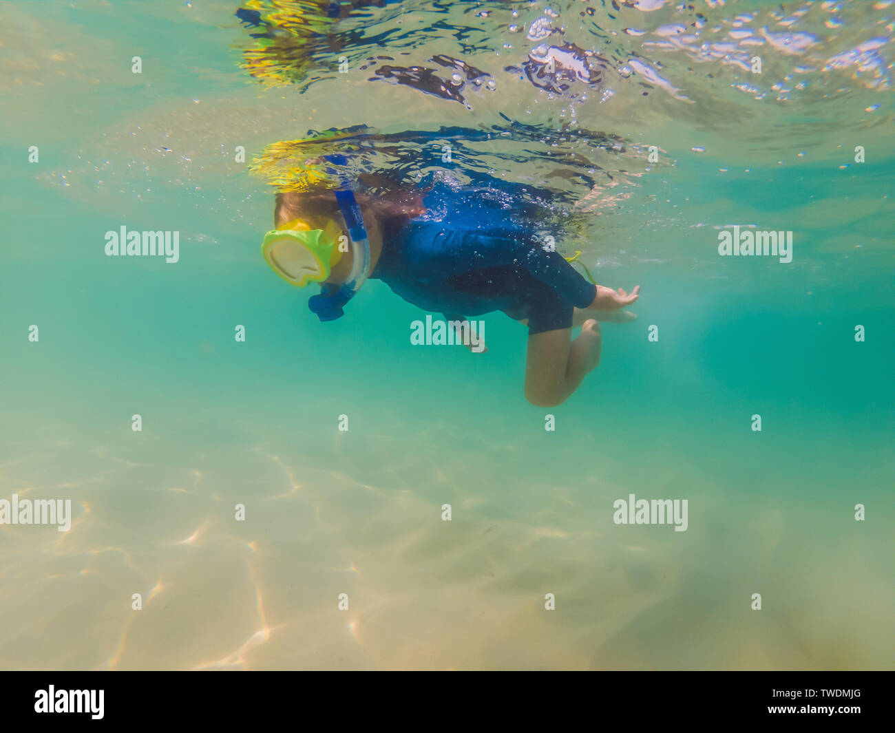 Happy family - active kid in snorkeling mask dive underwater, see tropical fish in coral reef sea pool. Travel adventure, swimming activity on summer - Stock Image
