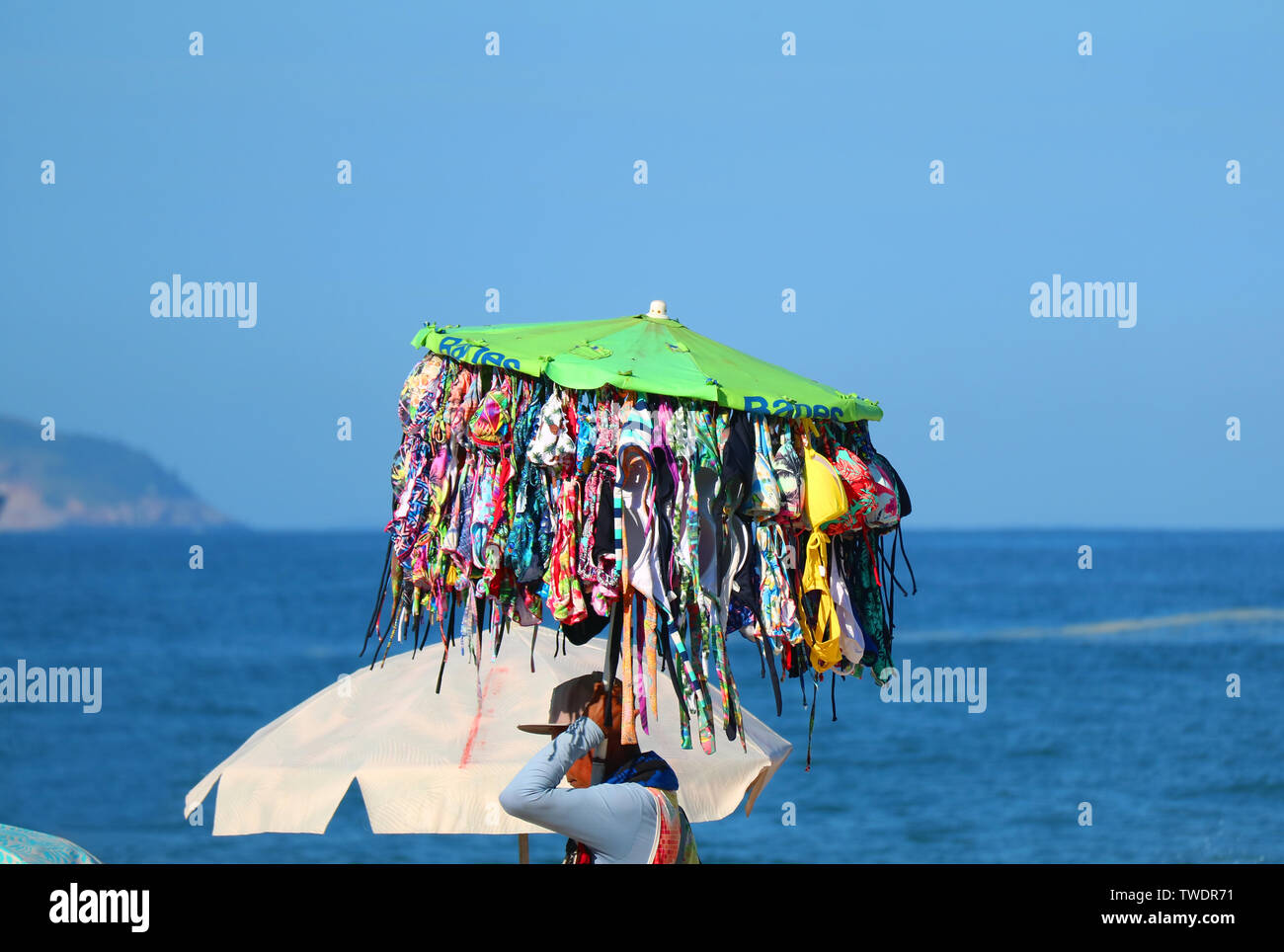 Swimming suit' seller carrying a lot of bikinis walking along the beach with the ocean in background - Stock Image