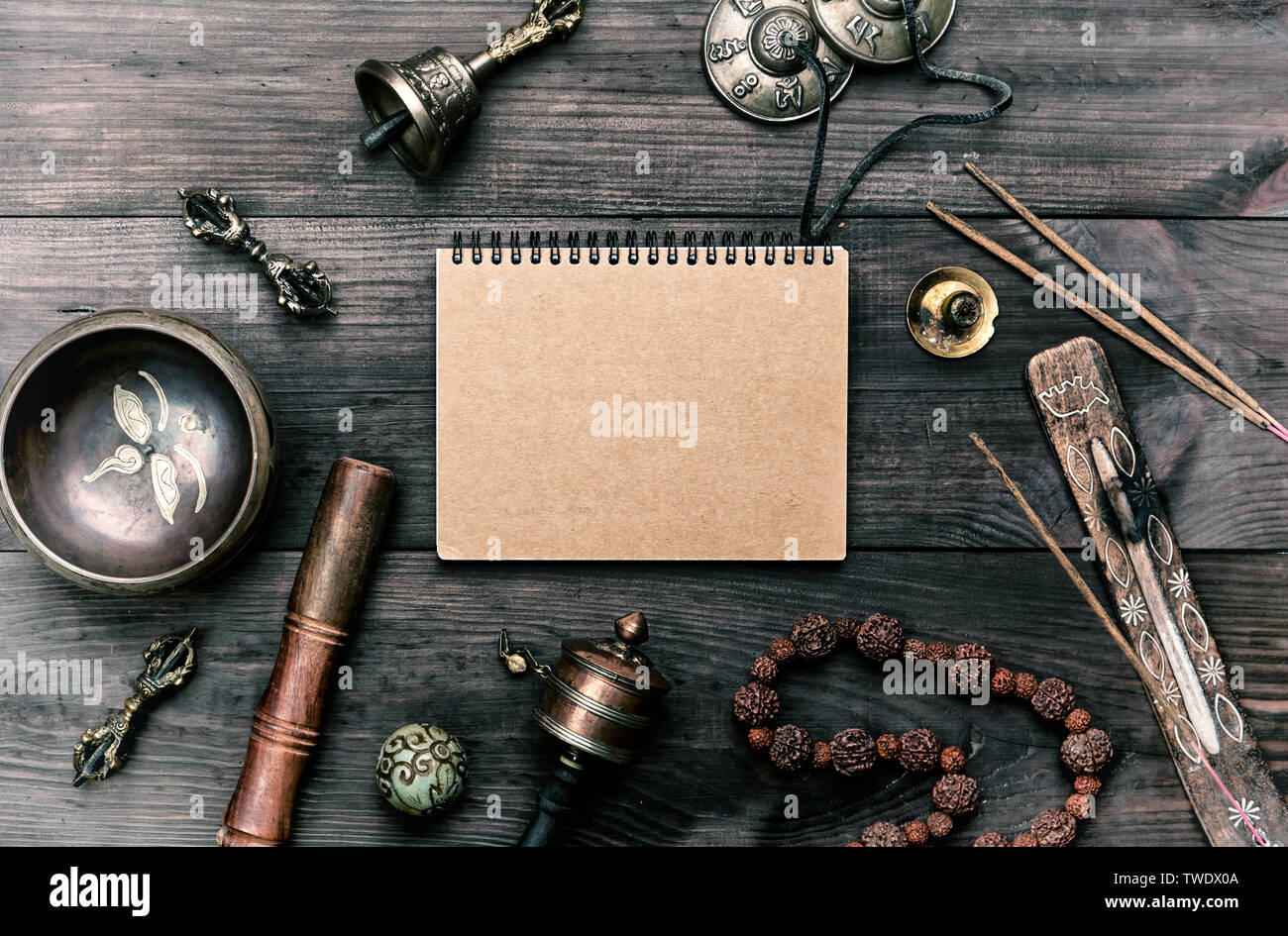 religious musical instruments for meditation and alternative medicine, blank notebook with brown sheets on a wooden background, top view - Stock Image
