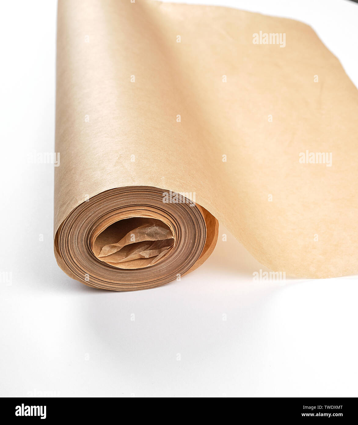 rolled brown parchment paper roll for baking on a white background - Stock Image