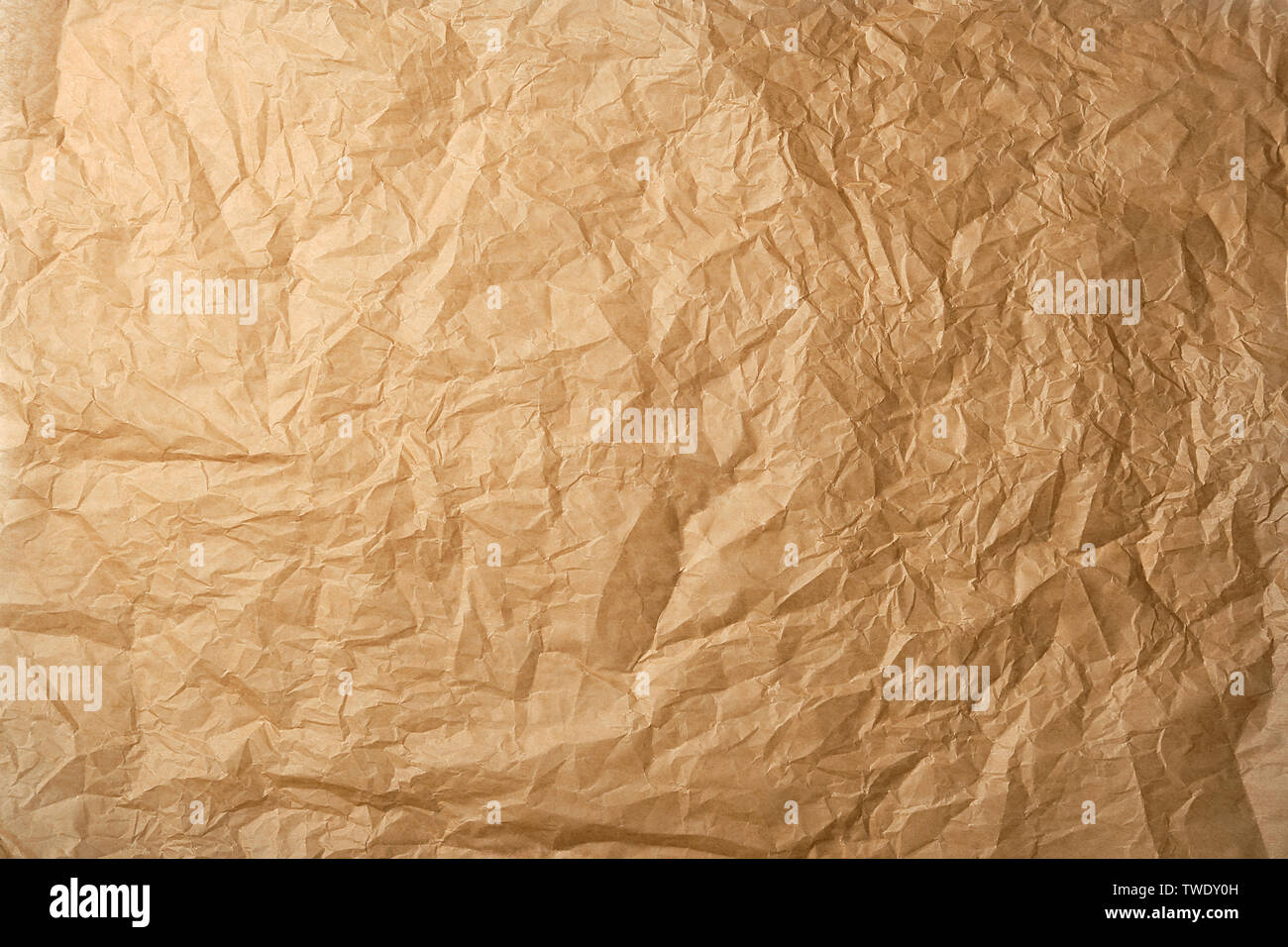 crumpled brown baking parchment paper, full frame - Stock Image