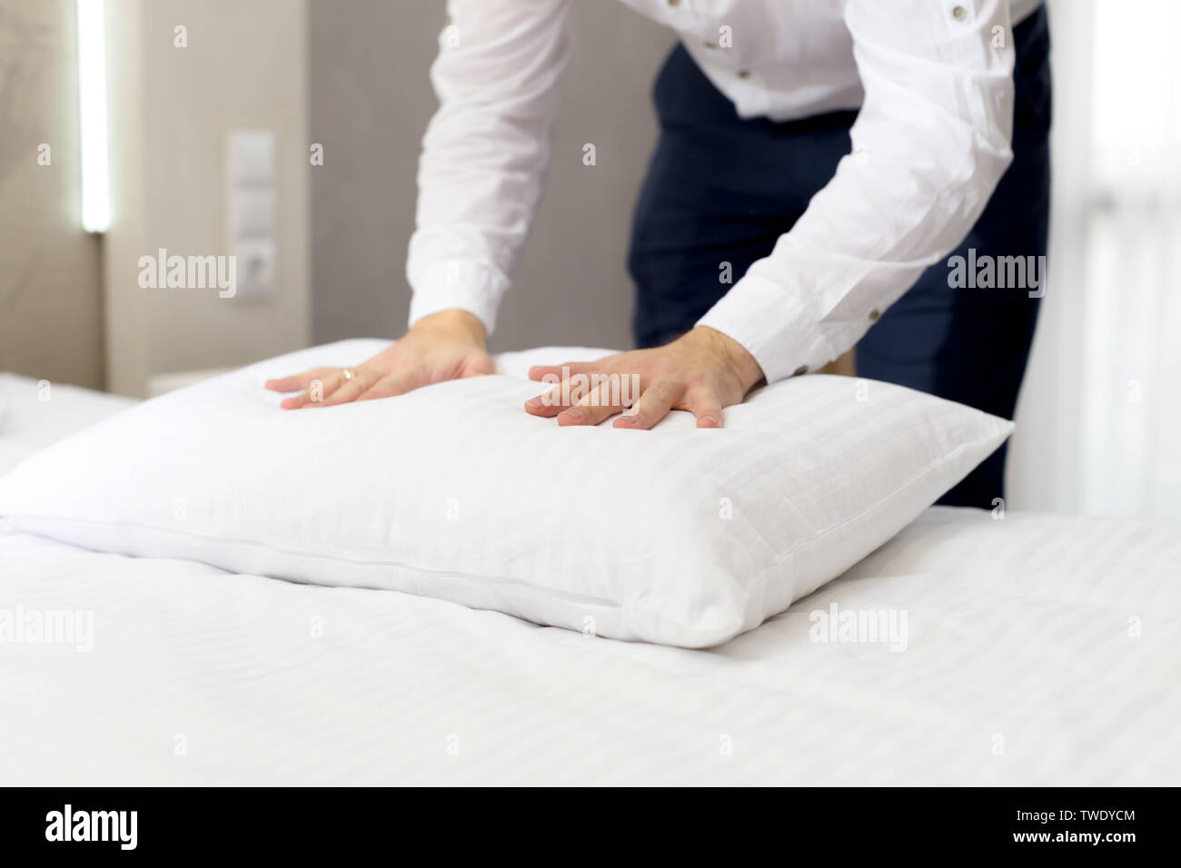 hotel staff setting up pillow on bed - Stock Image