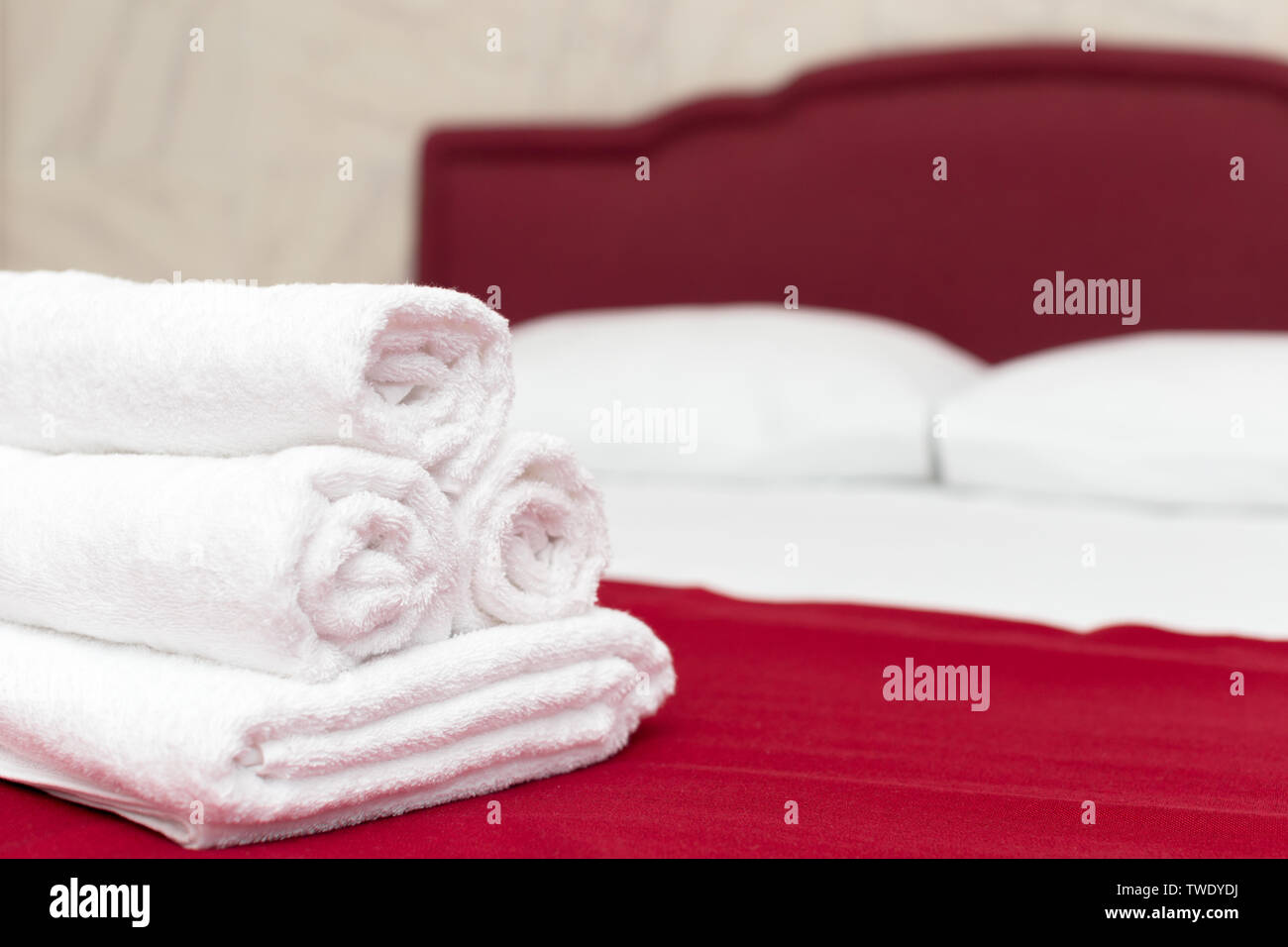 Clean towels on bed at hotel room - Stock Image