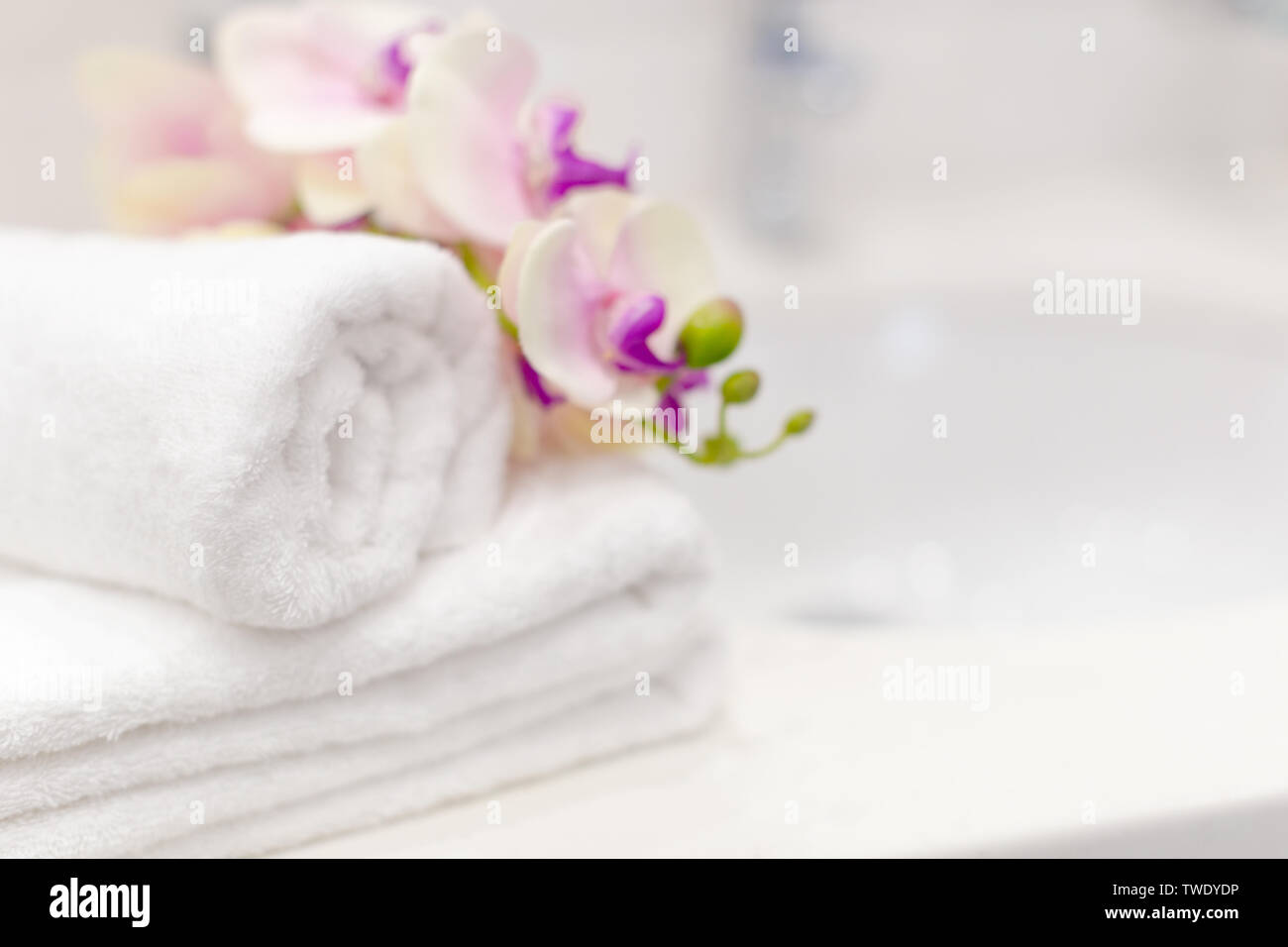 Stack of towels with flower decor in a hotel room - Stock Image